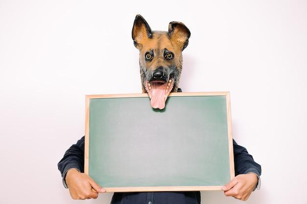 Persoon met hondenmasker houdt een leeg schoolbord vast