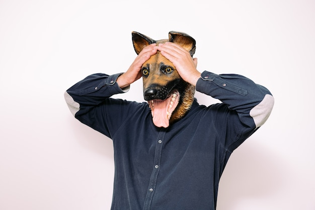 Persoon met hondenmasker houdt handen tegen hoofd in verrassing