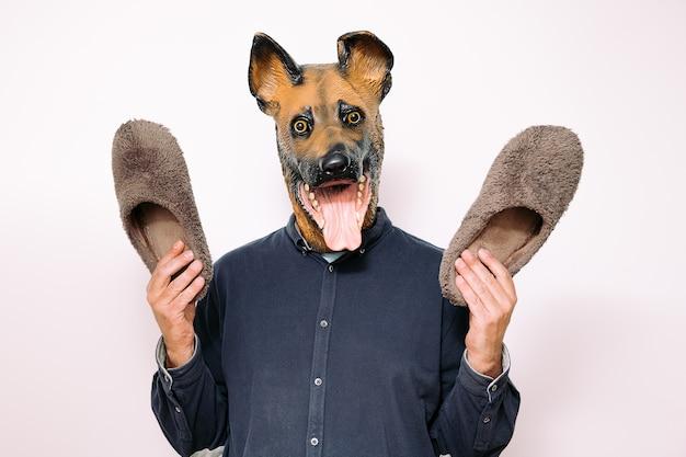 Persoon met hondenmasker laat een paar pantoffels zien