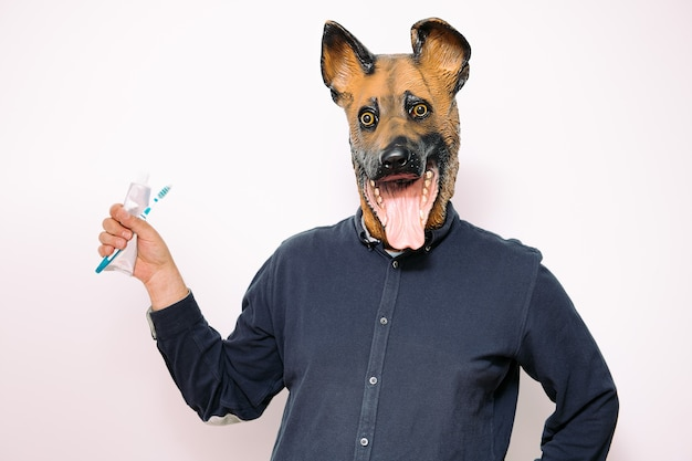 Persoon met hondenmasker met borstel en tandpasta