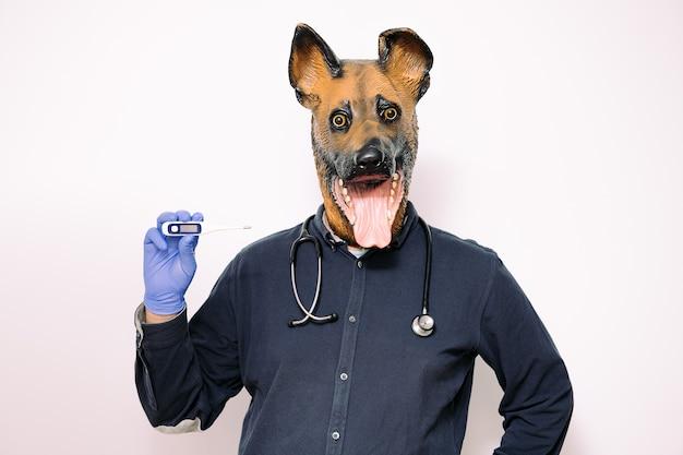 Persoon met hondenmasker met een thermometer