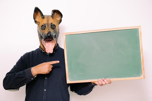 Persoon met hondenmasker wijst naar een leeg schoolbord