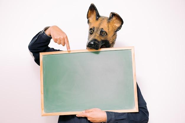 Persoon met hondenmasker wijst naar een onbeschreven blad