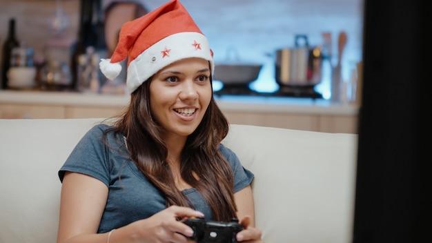 Persoon met kerstmuts die videogames wint met joystick
