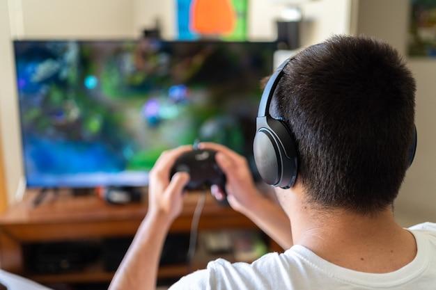 Persoon met koptelefoon en het spelen van videogames op tv