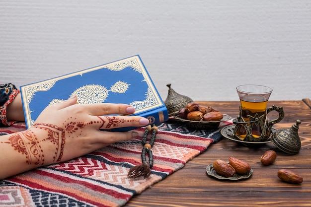 Persoon met mehndi die de koran vasthoudt in de buurt van theeglas