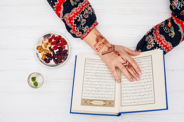 Persoon met mehndi die koran dichtbij droog fruit leest