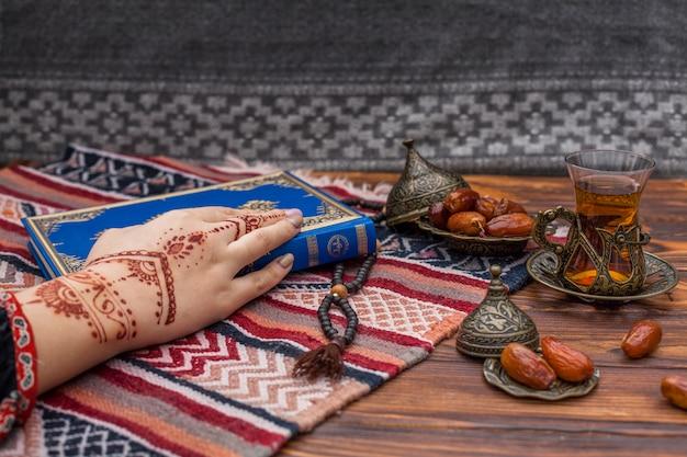 Persoon met mehndi die koranboek houdt dichtbij thee