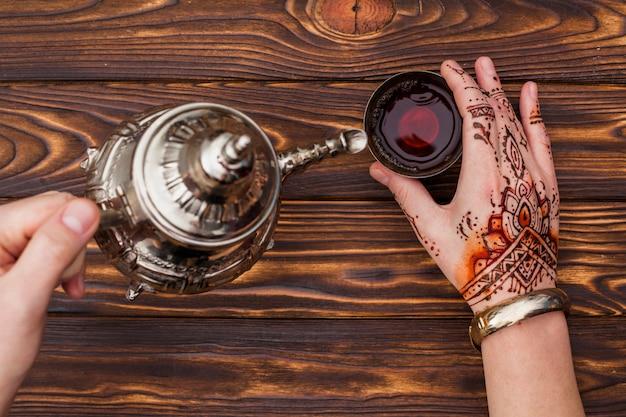 Persoon met mehndi die thee in kleine kop giet