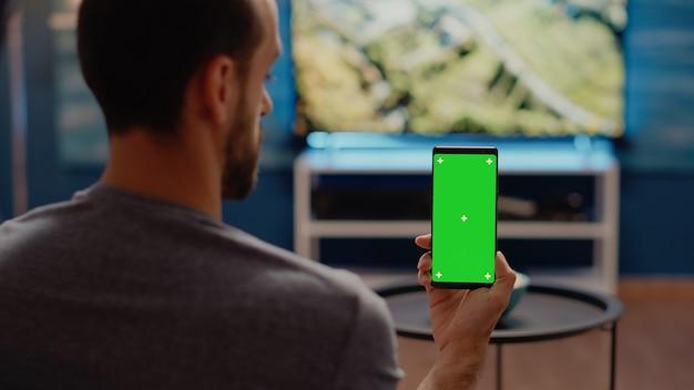 Persoon met moderne smartphone die naar groen scherm kijkt