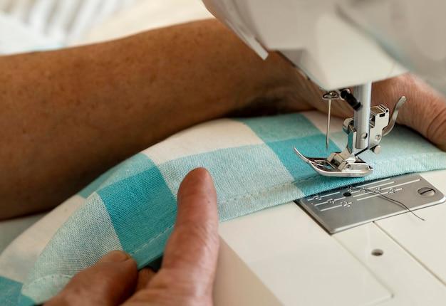 Persoon met naaimachine en textiel