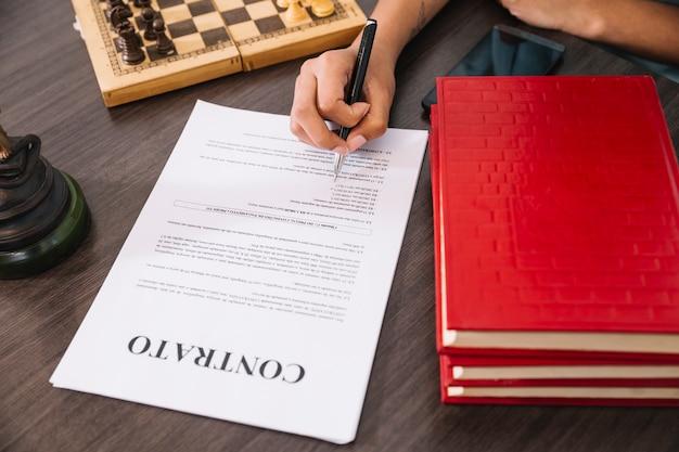 Persoon met pen schrijven in document aan tafel met smartphone, boeken en schaken