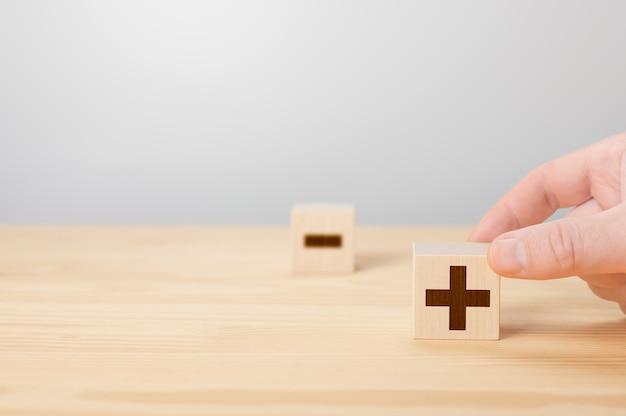 Persoon met plustekenblok tegen min plus of min man houdt kubus met pluspictogram vast