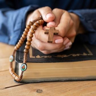 Persoon met rozenkrans in handen en bidden