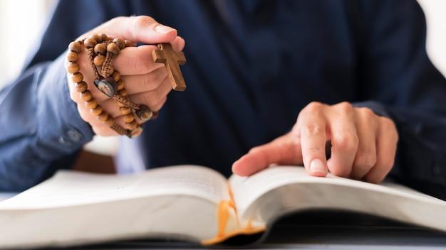 Persoon met rozenkrans met kruis en bidden