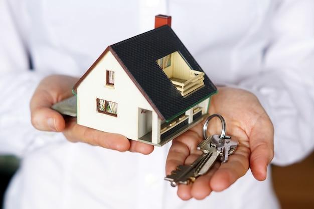 Persoon met sleutels en model huis