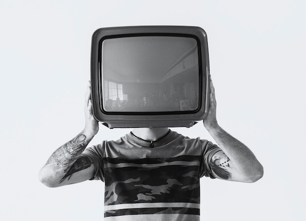 Persoon met tatoeage die televisie vasthoudt
