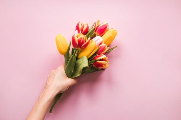 Persoon met tulpen boeket in de hand