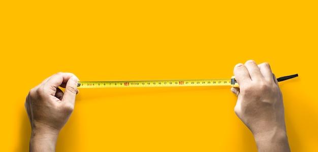 Persoon met tweedehands trekkende meetlint, handgereedschap voor het meten van lengte, geïsoleerd op gele achtergrond en uitknippad.