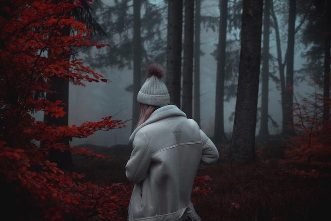 Persoon met witte jas en witte hoed in bos