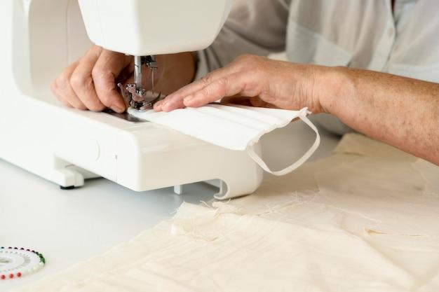 Persoon naaien gezichtsmasker met behulp van machine