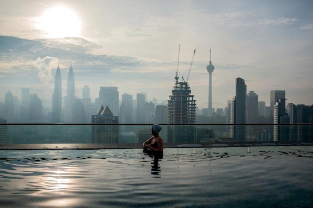 Persoon ontspannen in het zwembad en genieten van het panorama van de stad. kuala lumpur, maleisië