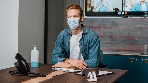 Persoon op kantoor met medisch masker