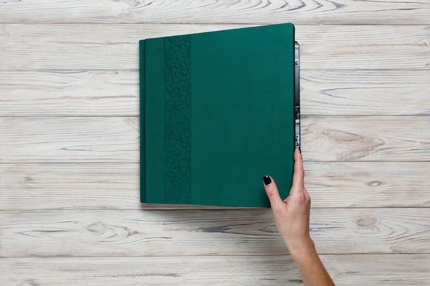 Persoon open fotoboek met decor. familie helder fotoalbum. vrouw hand met bruiloft fotoalbum