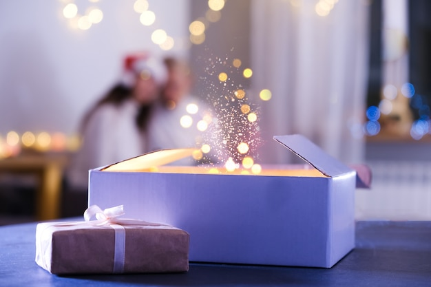 Persoon opent cadeau, wonderen en wensen komen uit op kerstavond. close-up handen met nieuwjaar thuis 's nachts aanwezig. magische achtergrond met stof en lichten in 2021