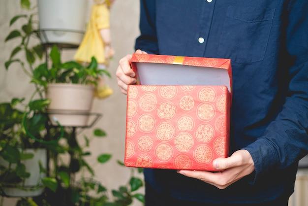 Persoon opent de geschenkdoos en controleert wat erin zit, verrassing op de feestdagen