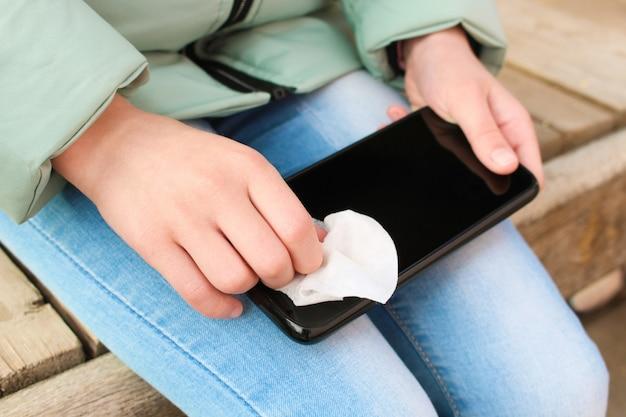 Persoon reinigt mobiele telefoon met natte doekjes.
