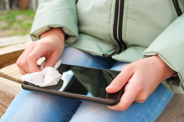 Persoon reinigt mobiele telefoon met vochtige doekjes.