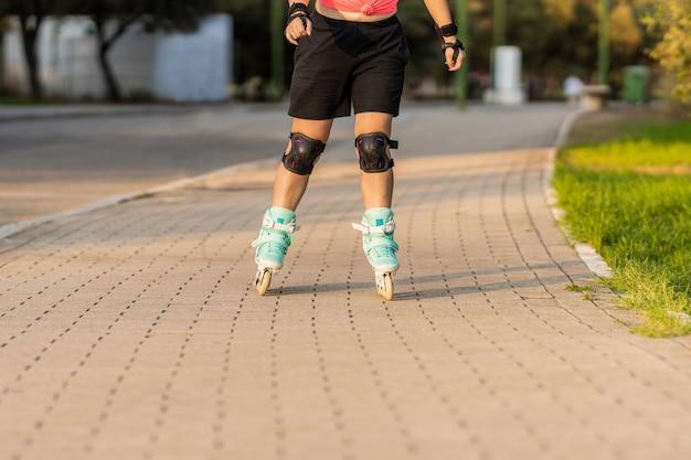 Persoon schaatsen met inline blauwe skates in een pad naast een park