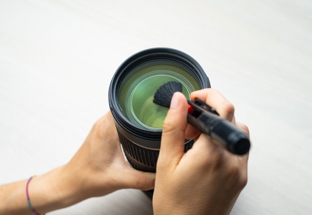 Persoon schoonmakende lens met penborstel op wit