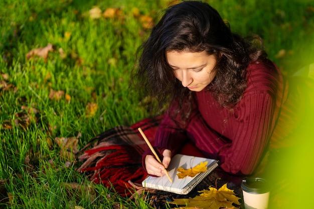 Persoon schrijft notities liggend op het gazon in het herfstpark. eenzaamheid met jezelf.