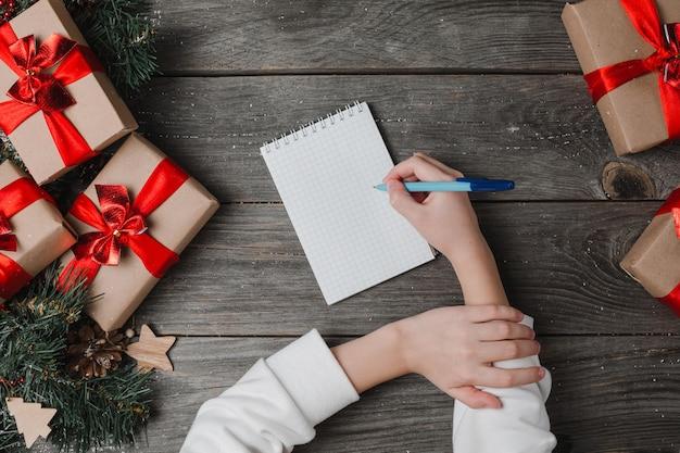 Persoon schrijft rond in notebook kerstcadeaus. menselijke handen kerstcadeautjes met lint