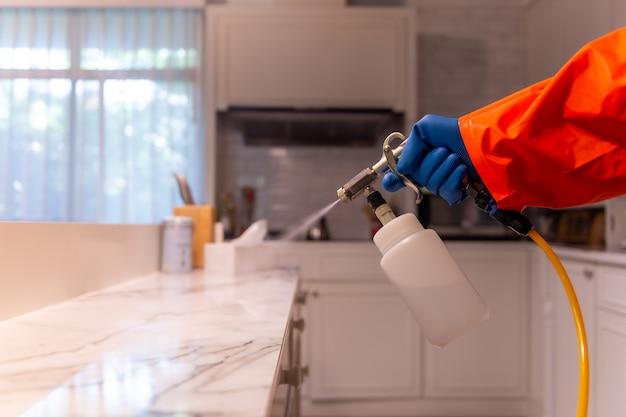 Persoon spuit het huis om virussen en bacteriën te voorkomen