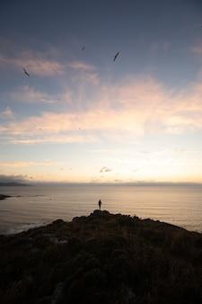 Persoon staande op de top van een heuvel aan zee bij zonsondergang - succes concept