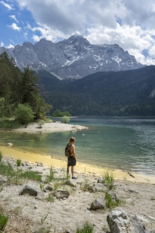 Persoon staande op het strand van het meer van de eibsee in duitsland, omringd door de bergen
