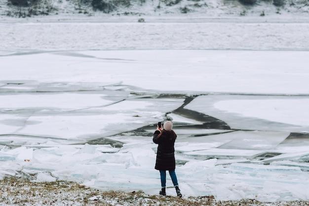 Persoon staat met haar rug naar de camera en neemt de foto van een bevroren rivier met ijsschotsen.