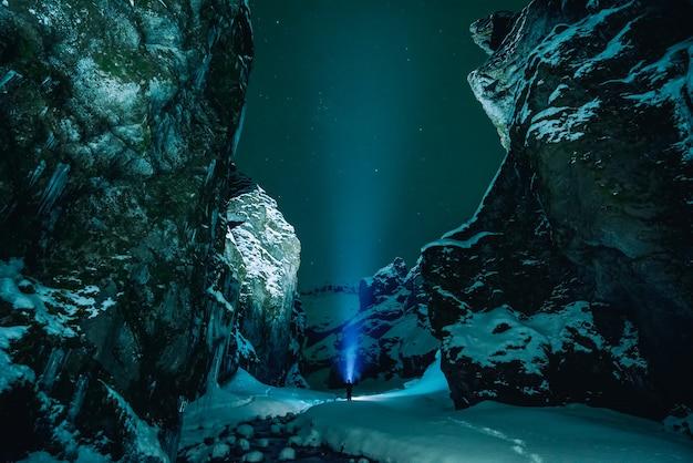 Persoon staat omringd door besneeuwde berg