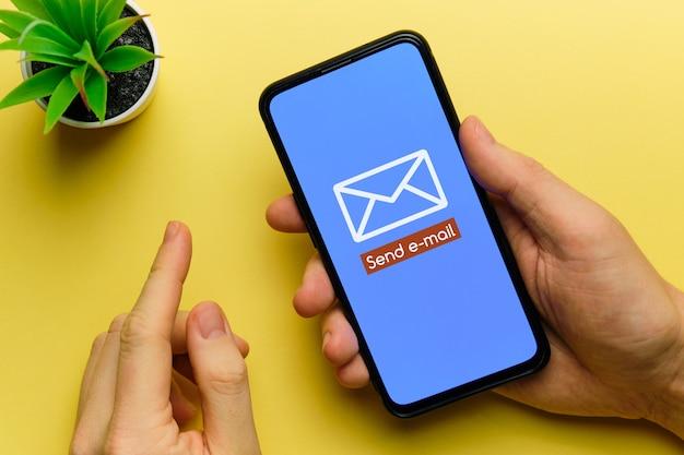 Persoon stuurt een e-mail met een smartphone in zijn handen.