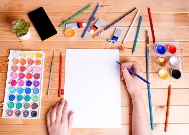 Persoon tekenen en schilderen. handen met een wit papier. uitzicht van boven.