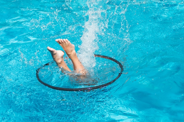 Persoon tussen hoelahoep duiken in het zwembad
