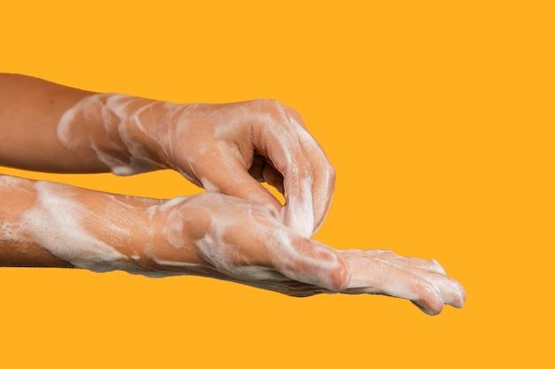 Persoon wassen van handen geïsoleerd op oranje