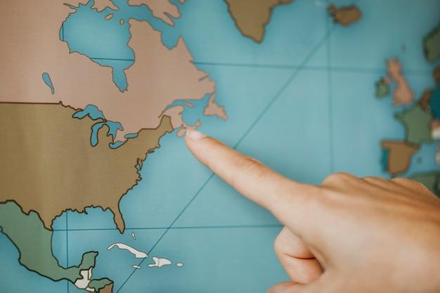 Persoon wijst naar noord-amerika op de kaart