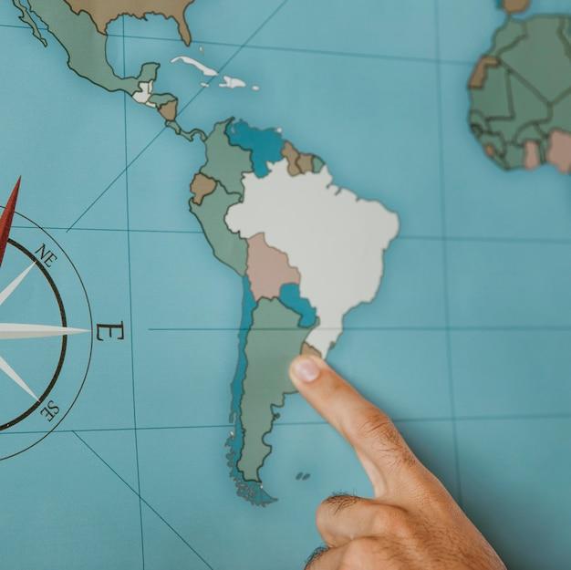 Persoon wijst naar zuid-amerika op de kaart