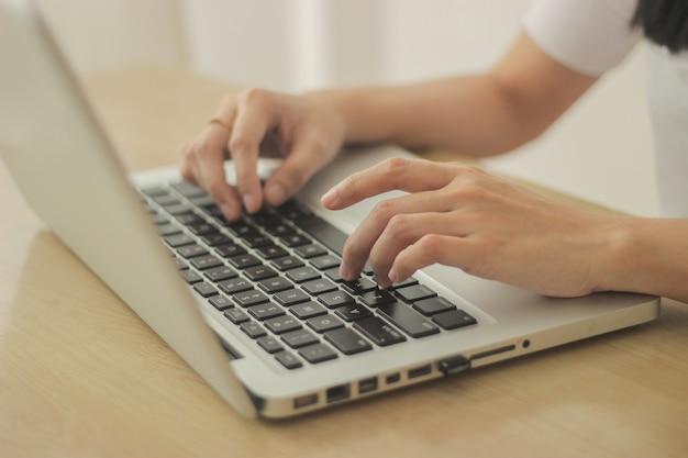 Persoon zit achter een bureau en typt op het toetsenbord van de laptop