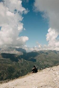 Persoon zit op de rand van een rotsachtige berg