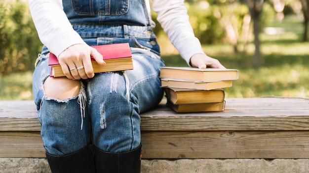 Persoon zittend op een tafel met boeken in het park